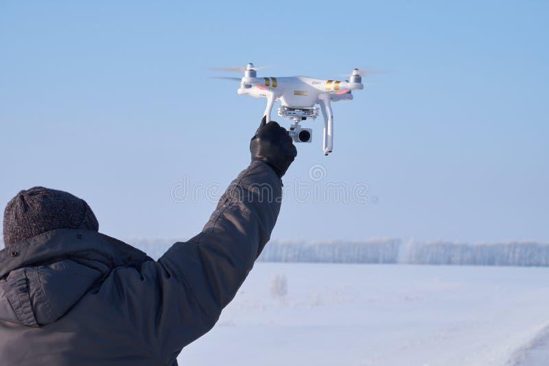Άτομο με Copter φανταστικό υπό εξέταση στη χειμερινή εποχή Altai, Σιβηρία στοκ φωτογραφία
