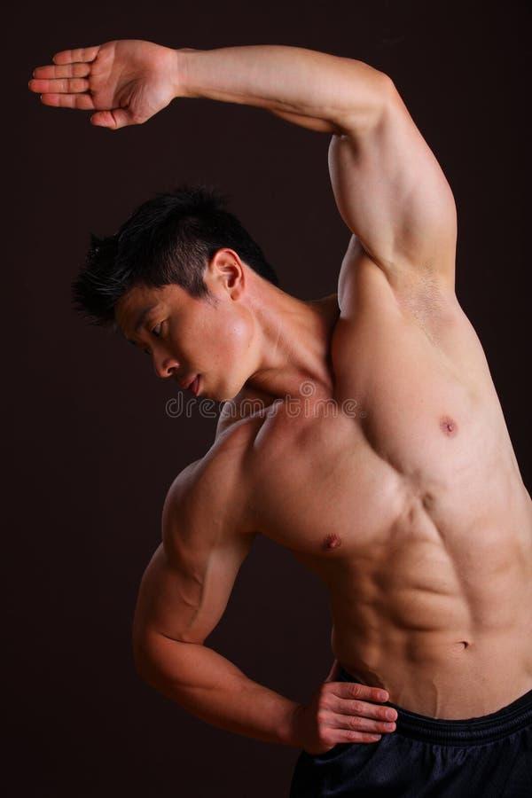 Άτομο μυών που τεντώνει τον αριστερούς βραχίονα και τα ABS στοκ εικόνα