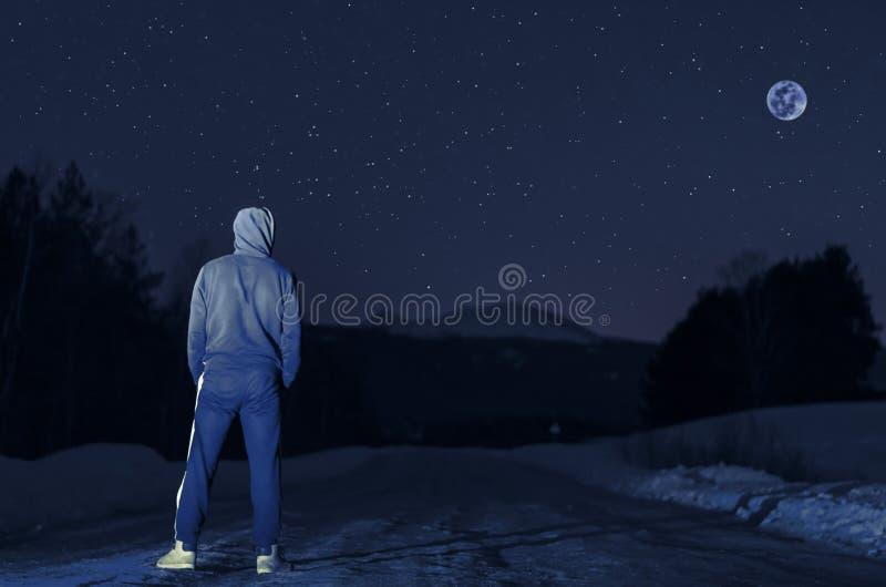 Άτομο νύχτας στο υπόβαθρο του βουνού στο χειμερινό δάσος στοκ εικόνες με δικαίωμα ελεύθερης χρήσης