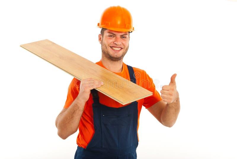 Άτομο οικοδόμων που φέρνει την ξύλινη σανίδα στοκ φωτογραφία με δικαίωμα ελεύθερης χρήσης
