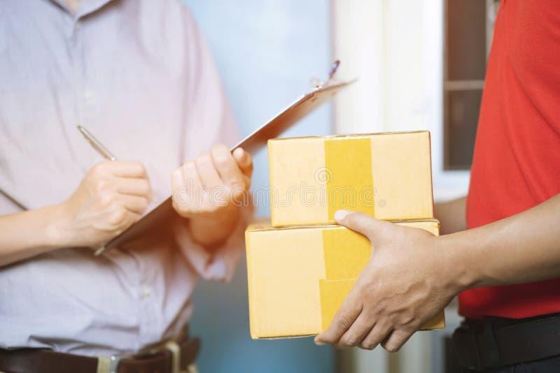 άτομο παράδοσης δεμάτων μιας συσκευασίας μέσω μιας υπηρεσίας και κλείστε επάνω τον πελάτη χεριών που δέχεται μια παράδοση στοκ φωτογραφίες με δικαίωμα ελεύθερης χρήσης