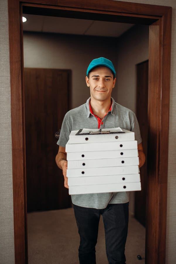 Άτομο παράδοσης με τη φρέσκια πίτσα στα κιβώτια χαρτοκιβωτίων στοκ εικόνα με δικαίωμα ελεύθερης χρήσης