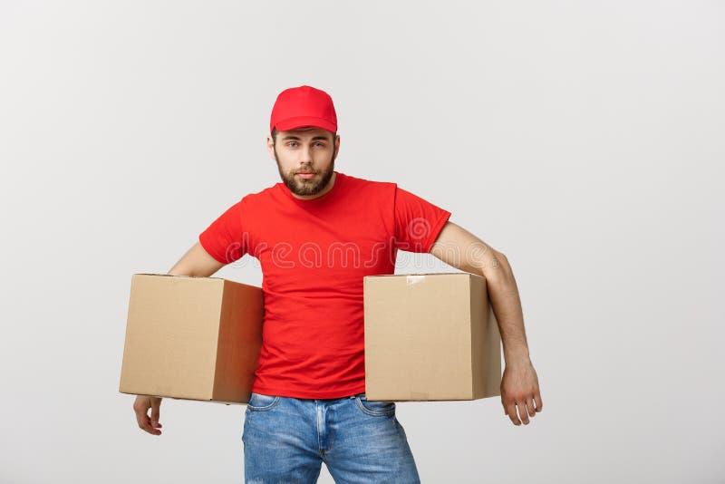 Άτομο παράδοσης πορτρέτου στην ΚΑΠ με την κόκκινη μπλούζα που λειτουργεί ως αγγελιαφόρος ή έμπορος που κρατά δύο κενά κουτιά από  στοκ εικόνες με δικαίωμα ελεύθερης χρήσης