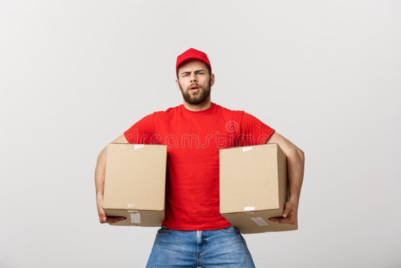 Άτομο παράδοσης πορτρέτου στην ΚΑΠ με την κόκκινη μπλούζα που λειτουργεί ως αγγελιαφόρος ή έμπορος που κρατά δύο κενά κουτιά από  στοκ φωτογραφίες με δικαίωμα ελεύθερης χρήσης