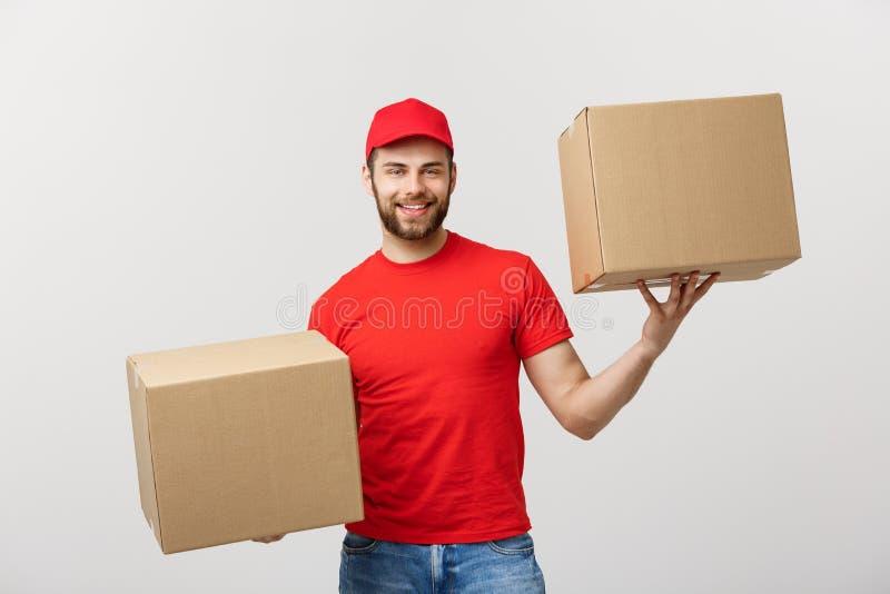 Άτομο παράδοσης πορτρέτου στην ΚΑΠ με την κόκκινη μπλούζα που λειτουργεί ως αγγελιαφόρος ή έμπορος που κρατά δύο κενά κουτιά από  στοκ εικόνες