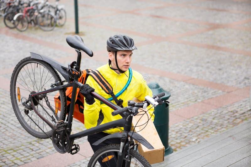 Άτομο παράδοσης αγγελιαφόρων με τη συσκευασία και το ποδήλατο στοκ εικόνα με δικαίωμα ελεύθερης χρήσης