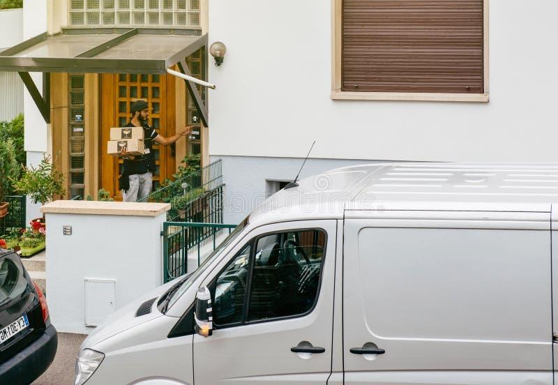 Άτομο παράδοσης με το δέμα στην πόρτα στοκ φωτογραφία με δικαίωμα ελεύθερης χρήσης
