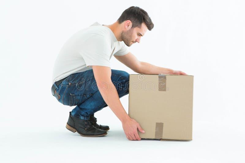 Άτομο παράδοσης που σκύβει επιλέγοντας το κουτί από χαρτόνι στοκ εικόνα