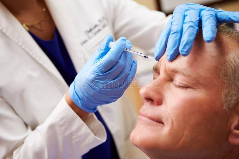 Άτομο που έχει την επεξεργασία Botox στην κλινική ομορφιάς στοκ εικόνα με δικαίωμα ελεύθερης χρήσης