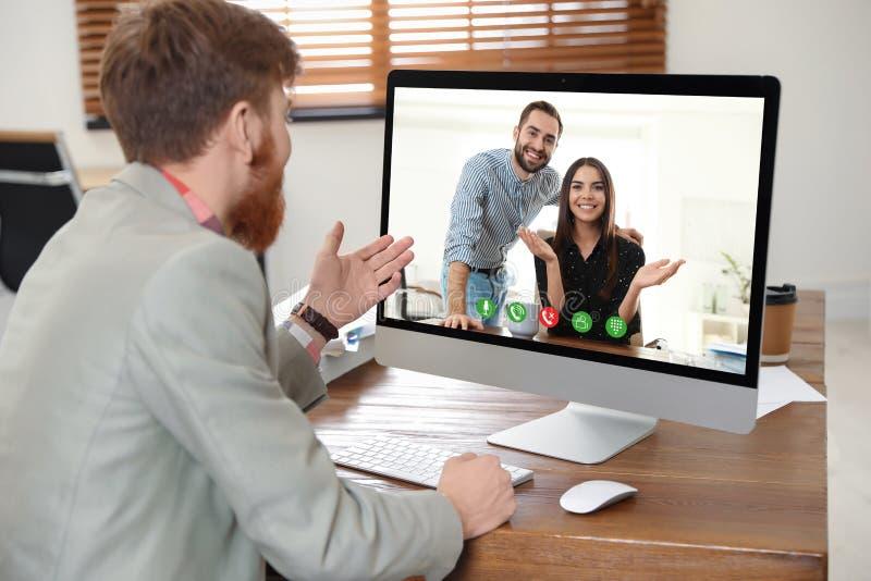 Άτομο που έχει την τηλεοπτική συνομιλία με τους συναδέλφους στον πίνακα στοκ εικόνες