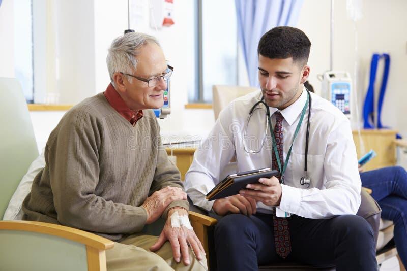 Άτομο που έχει τη χημειοθεραπεία με το γιατρό που χρησιμοποιεί την ψηφιακή ταμπλέτα στοκ εικόνα με δικαίωμα ελεύθερης χρήσης