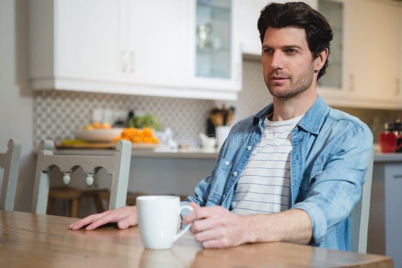Άτομο που έχει τον καφέ στην κουζίνα στο σπίτι στοκ εικόνες