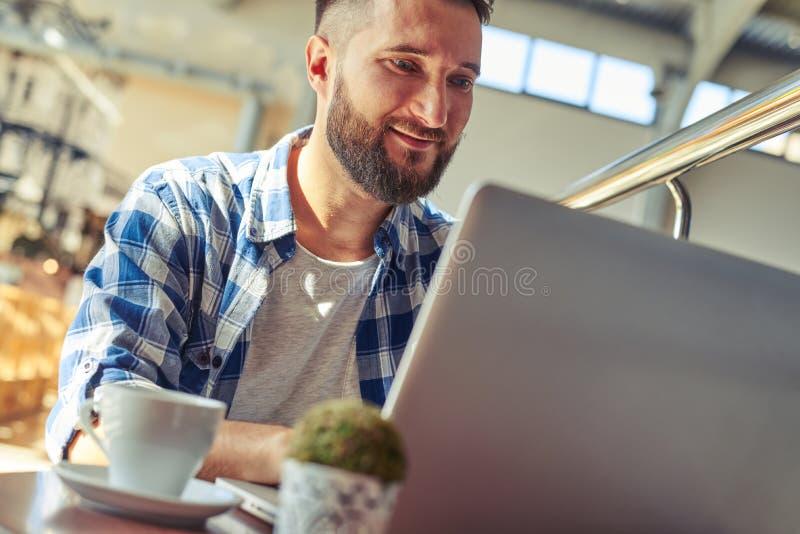 Άτομο που έχει το διάλειμμα και που εργάζεται με το lap-top στοκ εικόνα