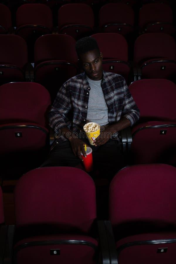 Άτομο που έχει το κρύα ποτό και popcorn προσέχοντας τον κινηματογράφο στοκ εικόνα