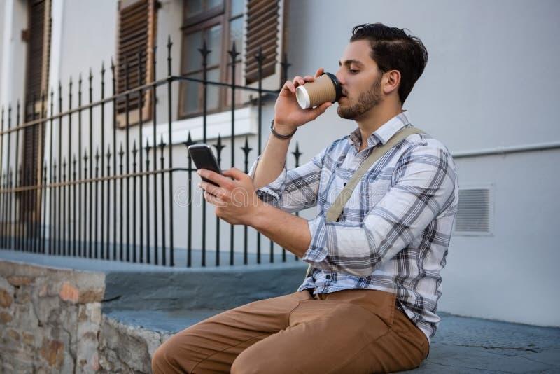 Άτομο που έχει το ποτό χρησιμοποιώντας το κινητό τηλέφωνο στοκ φωτογραφία