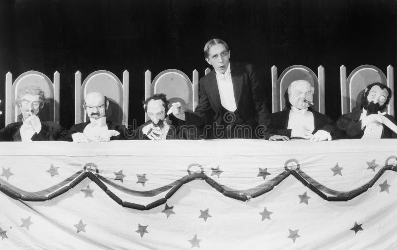 Άτομο που δίνει μια ομιλία με πέντε μαριονέτες χαρακτήρα που κάθονται στον πίνακα (όλα τα πρόσωπα που απεικονίζονται δεν ζουν περ στοκ φωτογραφία