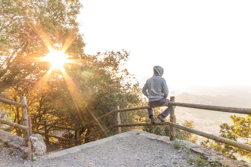 Άτομο που αγνοεί το όμορφο τοπίο στον πάγκο του βουνού στοκ εικόνα