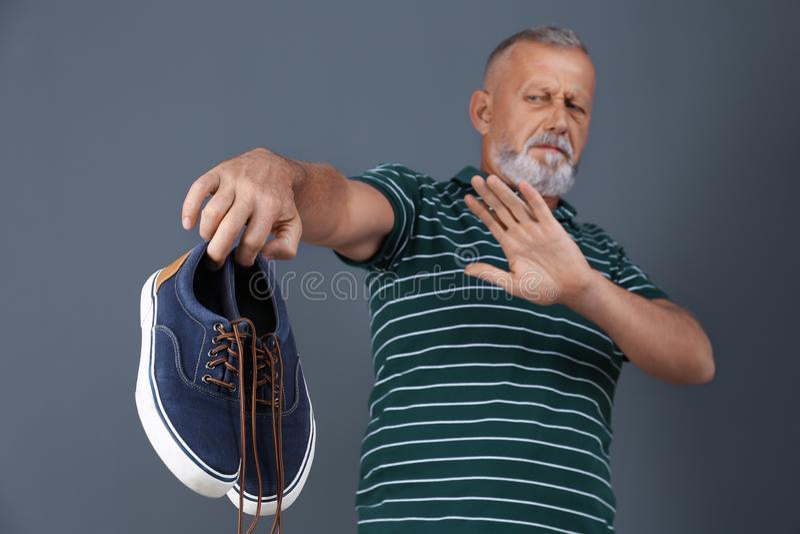 Άτομο που αισθάνεται την κακή μυρωδιά από τα παπούτσια στο υπόβαθρο χρώματος στοκ εικόνα με δικαίωμα ελεύθερης χρήσης