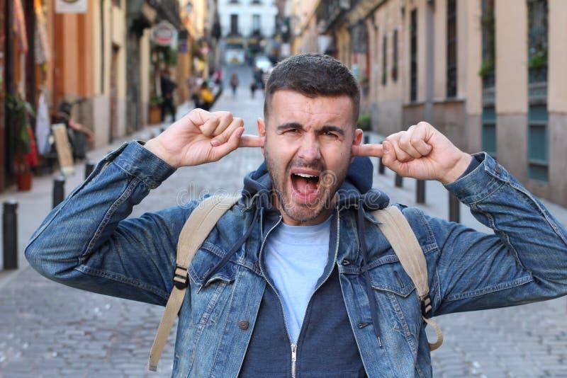 Άτομο που ακούει ένας αφόρητος θόρυβος στοκ φωτογραφία με δικαίωμα ελεύθερης χρήσης