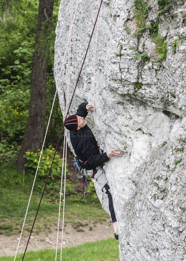 Άτομο που αναρριχείται στο δύσκολο τοίχο στοκ φωτογραφία