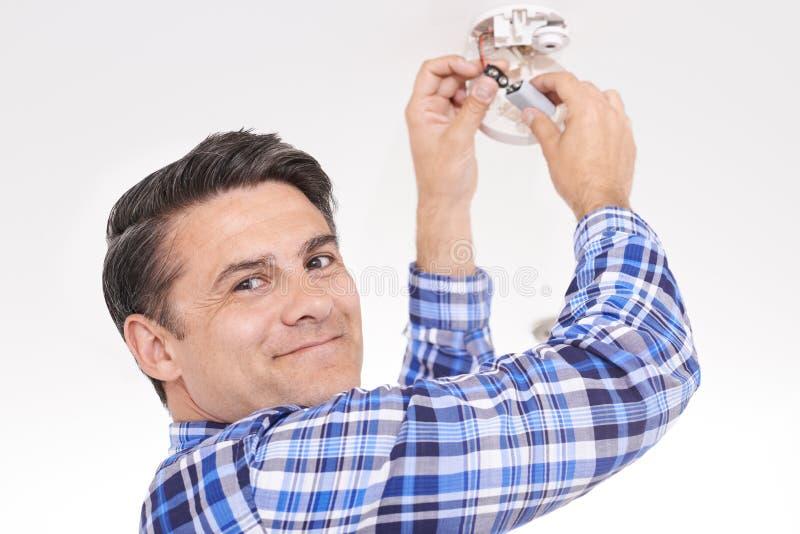 Άτομο που αντικαθιστά την μπαταρία στο συναγερμό εγχώριου καπνού στοκ εικόνα