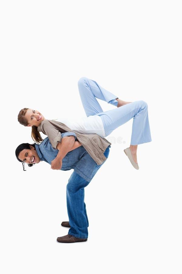 Άτομο που ανυψώνει τη φίλη του στην πλάτη του στοκ εικόνες με δικαίωμα ελεύθερης χρήσης