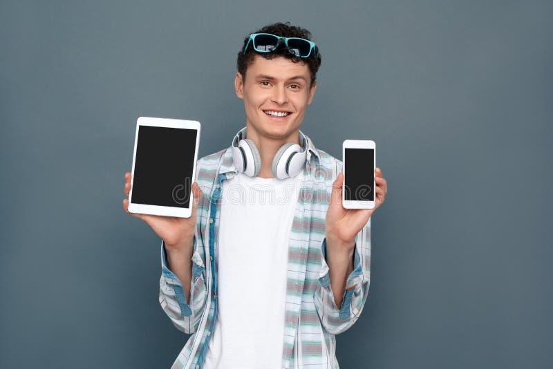 Άτομο που απομονώνεται στο γκρίζο smartphone εκμετάλλευσης στάσης έννοιας τουρισμού τοίχων και την ψηφιακή ταμπλέτα που φαίνονται στοκ φωτογραφία με δικαίωμα ελεύθερης χρήσης