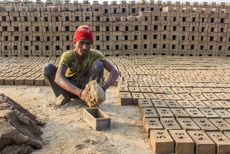 Άτομο που αφαιρεί τα τούβλα από τη φόρμα στοκ φωτογραφίες