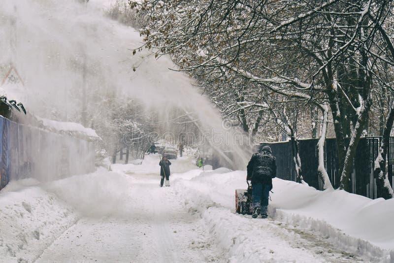 Άτομο που αφαιρεί το χιόνι από την οδό της Μόσχας που χρησιμοποιεί τον ανεμιστήρα χιονιού στοκ εικόνα