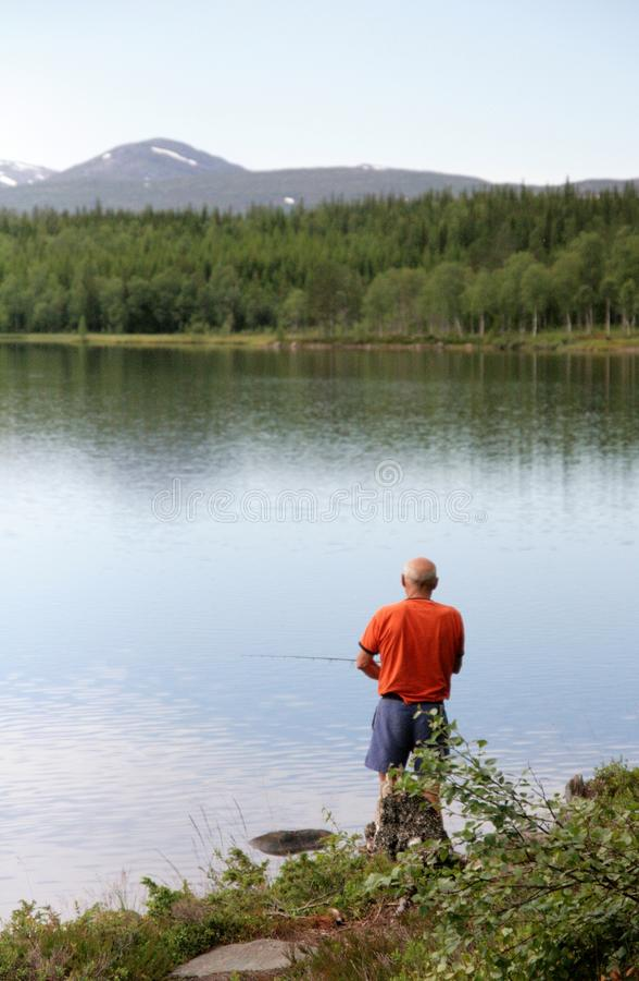 Άτομο που αλιεύει από μια λίμνη στοκ εικόνα με δικαίωμα ελεύθερης χρήσης