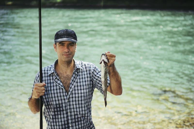 Άτομο που αλιεύει στον ποταμό και που παρουσιάζει ψάρια στη κάμερα στοκ εικόνα με δικαίωμα ελεύθερης χρήσης