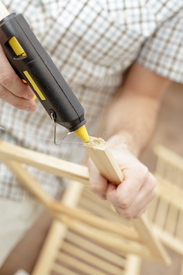 Άτομο που βάζει ένα ηλεκτρικό καυτό πυροβόλο όπλο κόλλας για τα ξύλινα έπιπλα στοκ φωτογραφίες