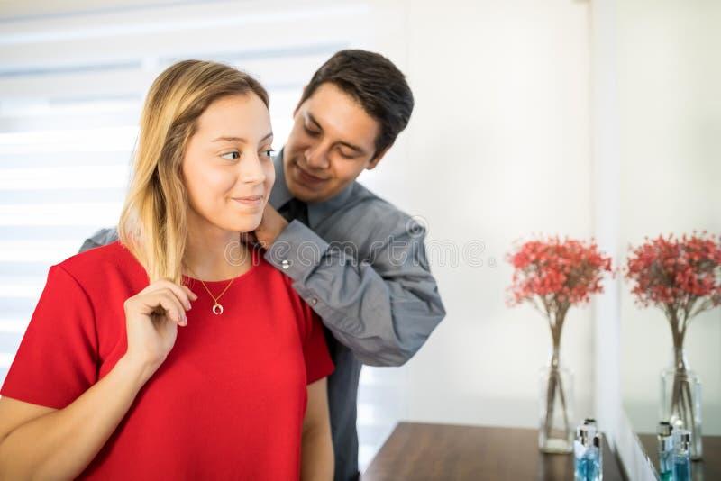 Άτομο που βάζει ένα περιδέραιο στο λαιμό συζύγων ` s στοκ εικόνες με δικαίωμα ελεύθερης χρήσης
