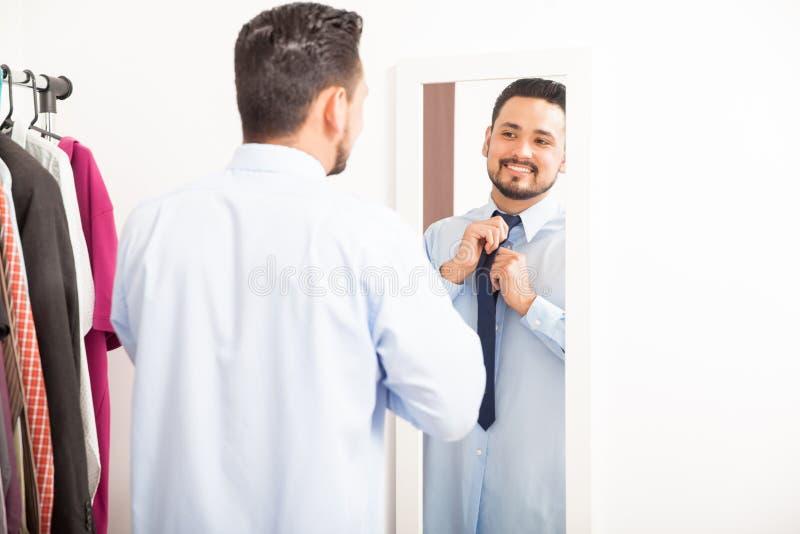Άτομο που βάζει στη γραβάτα σε ένα βεστιάριο στοκ φωτογραφία με δικαίωμα ελεύθερης χρήσης