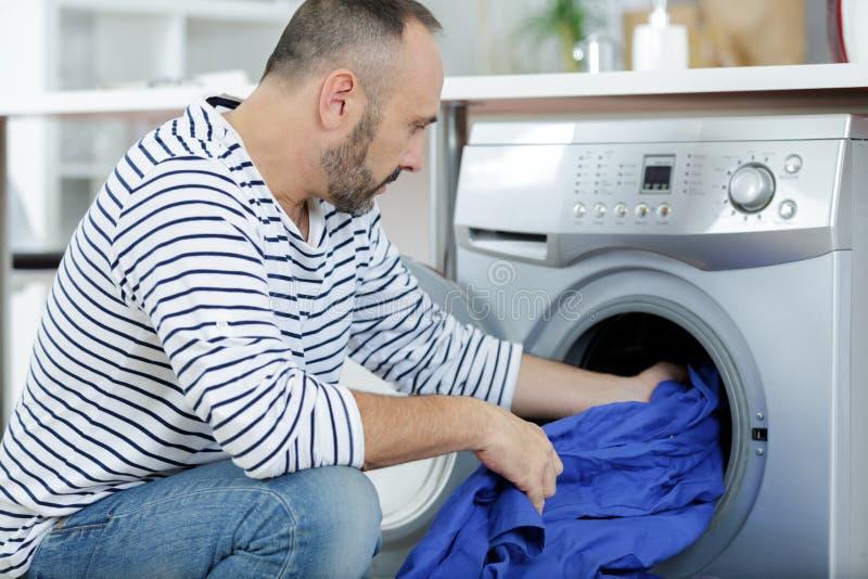 Άτομο που βάζει τα ενδύματα χρώματος στο πλυντήριο μέσα στην άποψη στοκ φωτογραφίες με δικαίωμα ελεύθερης χρήσης