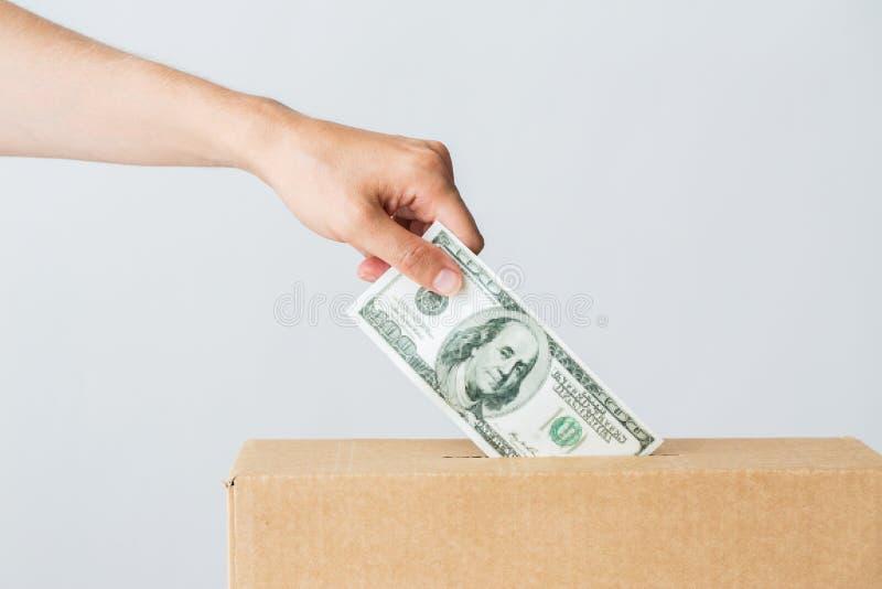Άτομο που βάζει τα χρήματα δολαρίων στο κιβώτιο δωρεάς στοκ εικόνες με δικαίωμα ελεύθερης χρήσης