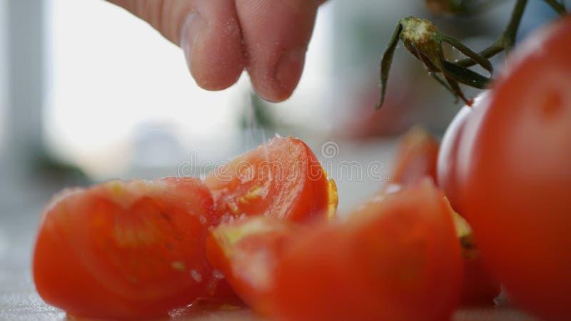 Άτομο που βάζει το άλας στις φέτες των κόκκινων ντοματών στοκ φωτογραφίες