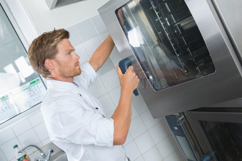 Άτομο που βάζει το δίσκο στο φούρνο στην κουζίνα στοκ φωτογραφίες