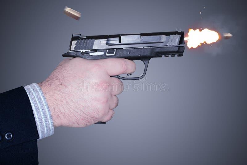 Άτομο που βάζει φωτιά σε ένα πυροβόλο όπλο στοκ εικόνα