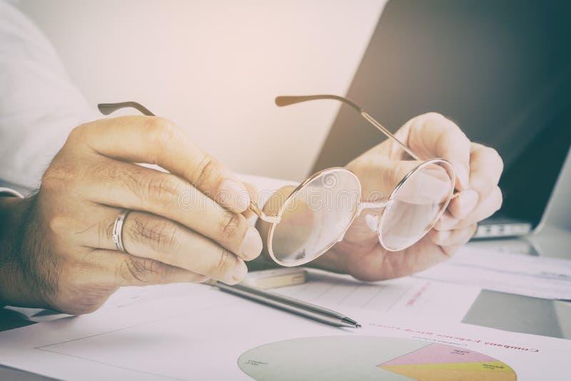 Άτομο που βάζει eyeglasses του για να έχει ένα αγαθό να κοιτάξει στο repor στοκ φωτογραφίες