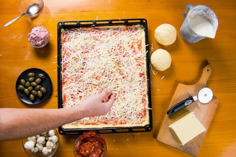 Άτομο που βάζει oregano προς την πίτσα στην παραγωγή στοκ φωτογραφία με δικαίωμα ελεύθερης χρήσης
