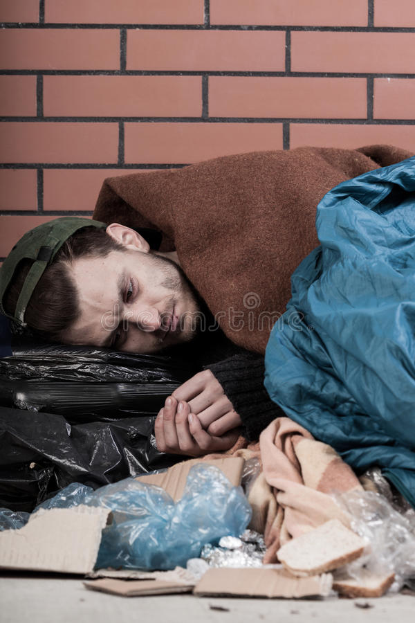 Άτομο που βρίσκεται στην οδό γύρω από τις τσάντες απορριμμάτων στοκ εικόνα με δικαίωμα ελεύθερης χρήσης