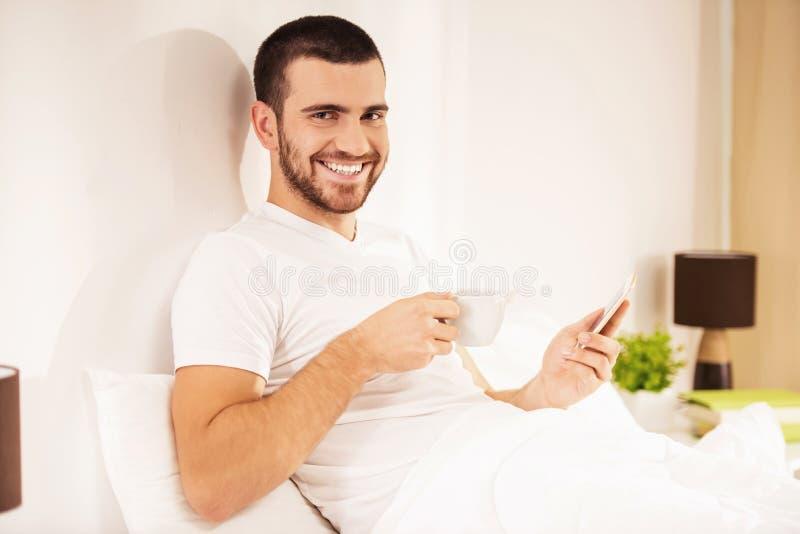 Άτομο που βρίσκεται στο κρεβάτι με Smartphone και το φλιτζάνι του καφέ στοκ φωτογραφία με δικαίωμα ελεύθερης χρήσης