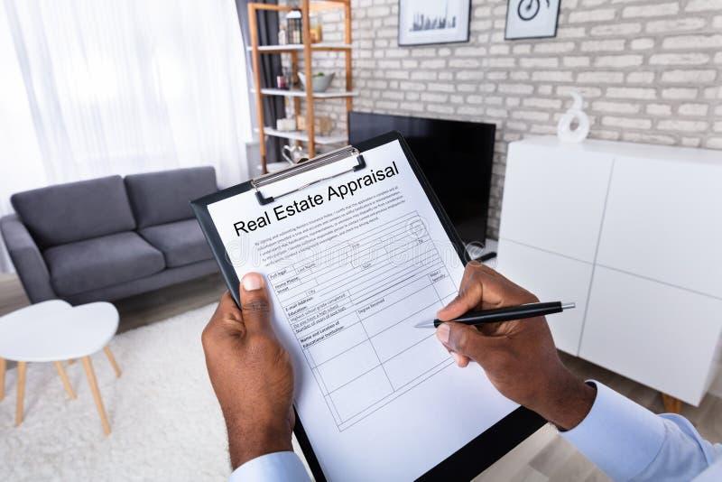 Άτομο που γεμίζει τη μορφή αξιολόγησης ακίνητων περιουσιών στοκ εικόνα με δικαίωμα ελεύθερης χρήσης