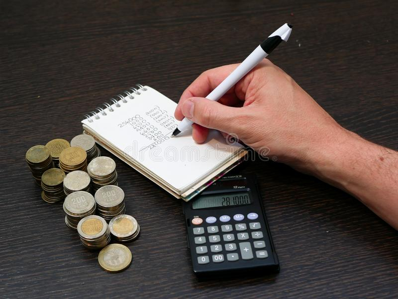 Άτομο που γράφει κάτω σε ένα σημειωματάριο μετρώντας τα κολομβιανά νομίσματα νομίσματος των διαφορετικών διορισμών πέρα από έναν  στοκ εικόνα