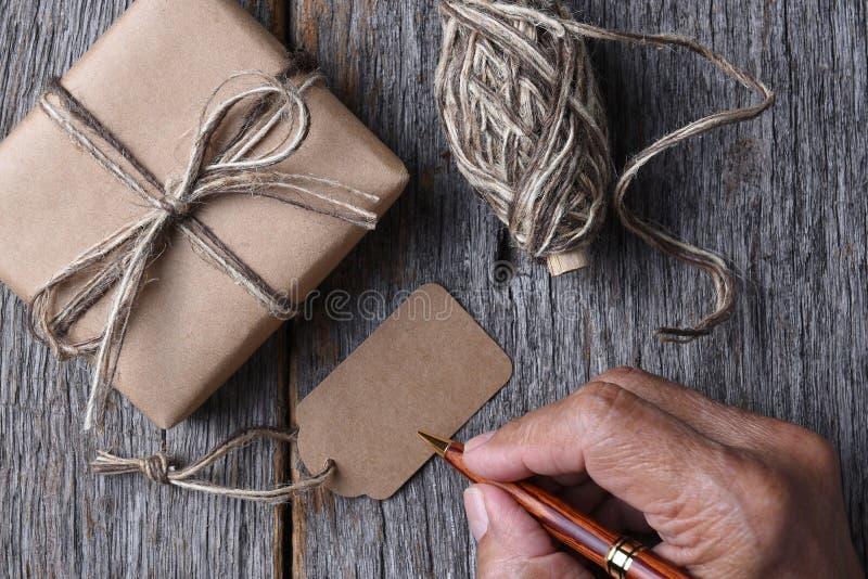 Άτομο που γράφει σε μια κενή ετικέττα δώρων Χριστουγέννων στοκ φωτογραφία με δικαίωμα ελεύθερης χρήσης