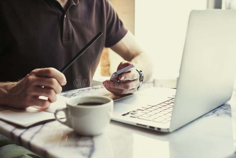 Άτομο που γράφει στο σημειωματάριο που χρησιμοποιεί το lap-top καθμένος στον καφέ που έχει τον καφέ Έννοια της νέας εργασίας επιχ στοκ εικόνες