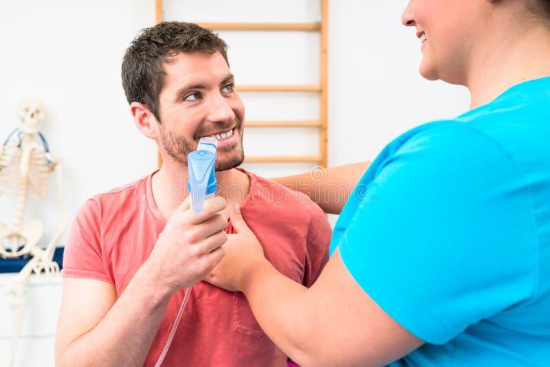 Άτομο που δίνει την πνευμονική εξέταση λειτουργίας με το επιστόμιο στο χέρι του στοκ φωτογραφία με δικαίωμα ελεύθερης χρήσης