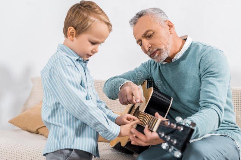 άτομο που δείχνει από το δάχτυλο διδάσκοντας το παιχνίδι εγγονών στην ακουστική κιθάρα στοκ φωτογραφίες με δικαίωμα ελεύθερης χρήσης