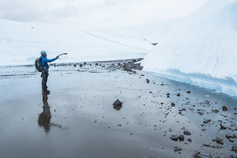 Άτομο που δείχνει με ένα τσεκούρι πάγου σε έναν απότομο τοίχο πάγου μπροστά από τον στοκ εικόνες